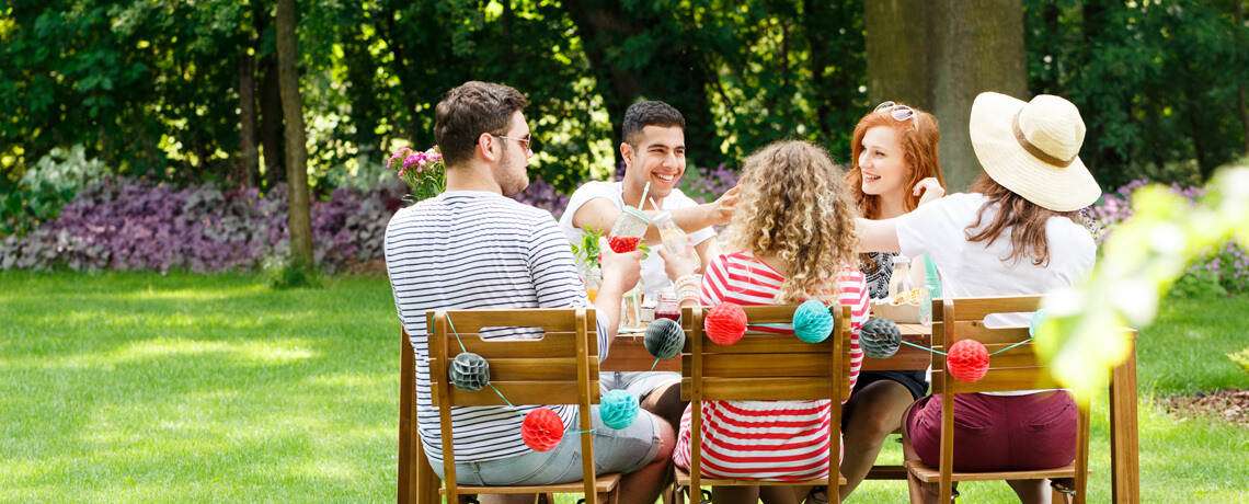 Outdoor lifestyle of group of young people chatting over bbq table